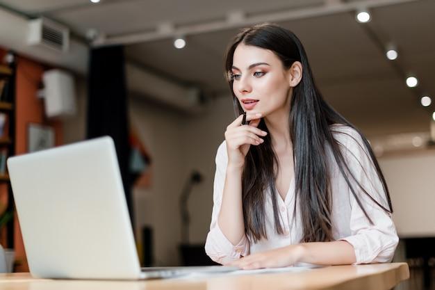 Vrouw die in het bureau met laptop werkt