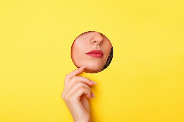 Vrouw die in het gat, heldere mooie make-up kijkt