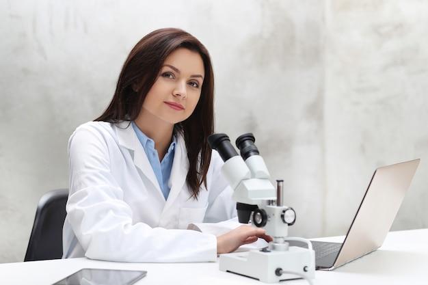 Vrouw die in het laboratorium met een microscoop werkt