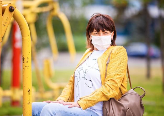 Vrouw die in het lentepark loopt dat beschermend wit medisch masker draagt