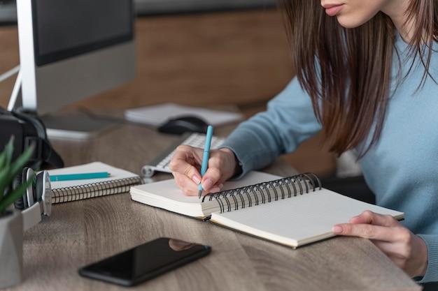 Vrouw die in het mediagebied werkt dat dingen op notitieboekje schrijft