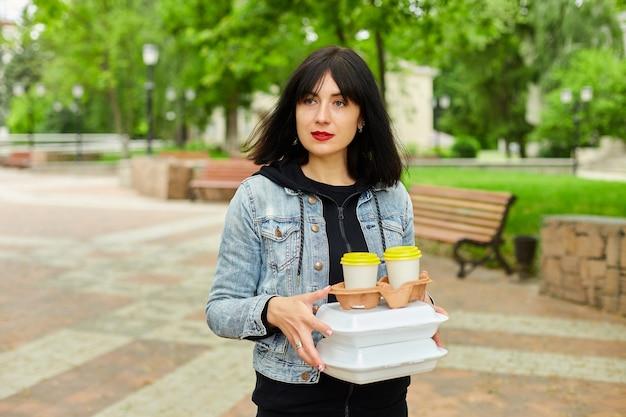 Vrouw die in het park loopt, een afhaalmaaltijd en koffie vasthoudt, lunchpauze heeft van het werk.