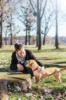 Vrouw die in het park met een hond geniet van