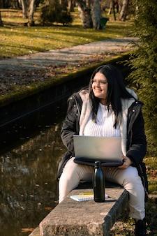 Vrouw die in het park met laptop werkt. buiten telewerken ivm coronavirus. online business.