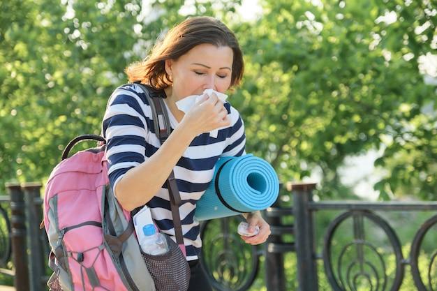 Vrouw die in het park met zakdoek loopt, en hoest niest