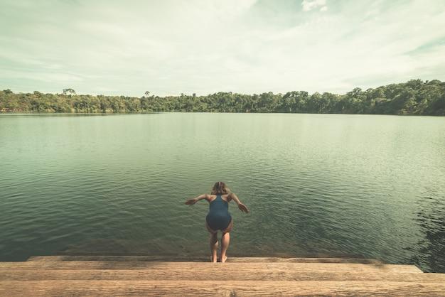 Vrouw die in het water van vulkanisch meer springt dat door bos in banlung wordt omringd