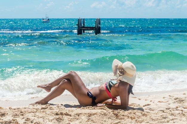 Vrouw die in het zand ligt dat het overzees bekijkt.