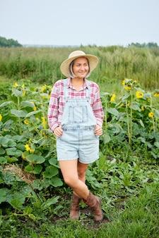 Vrouw die in hoed draagt die zich op organic bio farm bevindt. herfst plantaardige oogst.