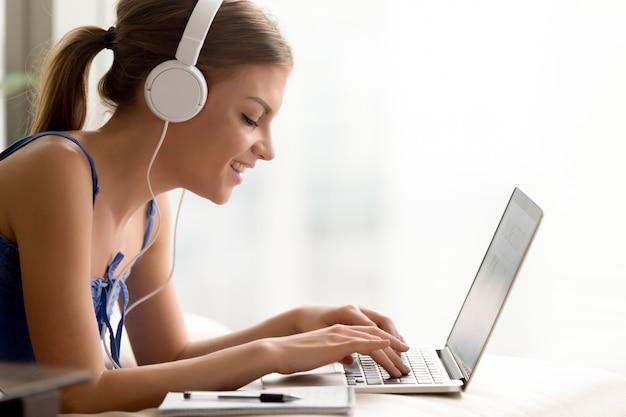 Vrouw die in hoofdtelefoon online taal leert