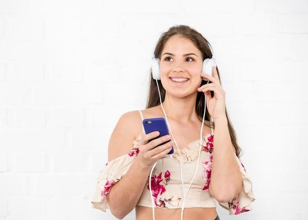 Vrouw die in hoofdtelefoons aan muziek en het glimlachen luistert