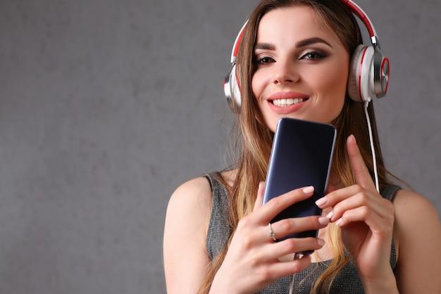 Vrouw die in hoofdtelefoons smartphone houdt