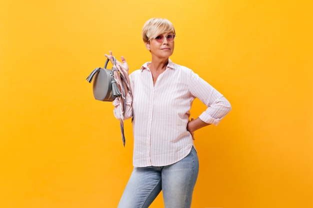 Vrouw die in jeans en roze overhemd grijze zak houdt