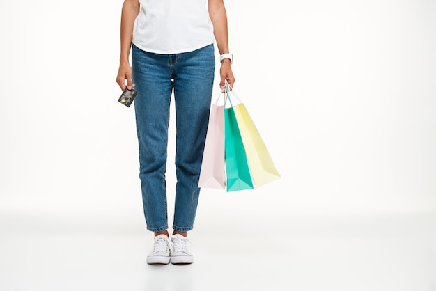 Vrouw die in jeans het winkelen zakken houdt