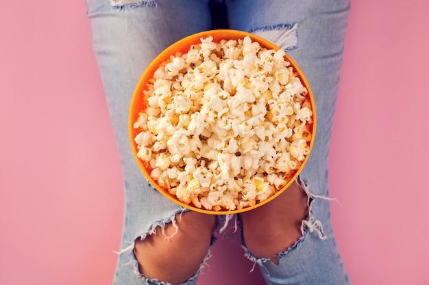 Vrouw die in jeans kom met popcorn houdt