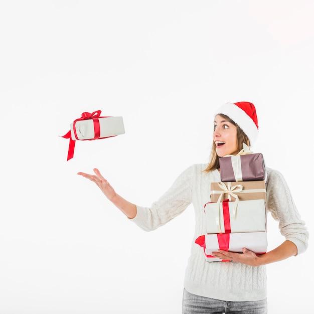 Vrouw die in kerstmanhoed giftdoos werpt