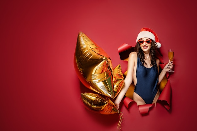 Vrouw die in kerstmanhoed gouden ballons houdt