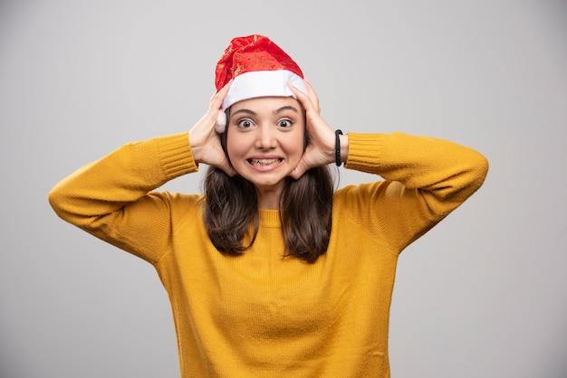 Vrouw die in kerstmanhoed haar gezicht op grijze muur houdt.