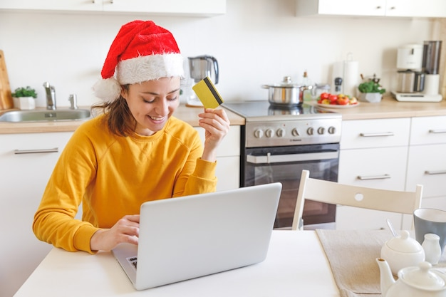 Vrouw die in kerstmanhoed online winkelt en met gouden creditcard betaalt