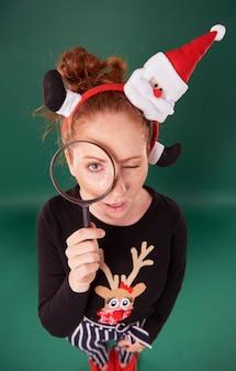 Vrouw die in kerstmiskleren door vergrootglas kijkt