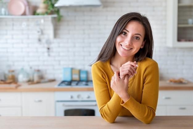Vrouw die in keuken de camera bekijkt