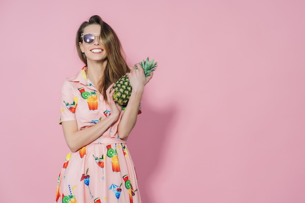 Vrouw die in kleurrijke kleding een ananas houdt