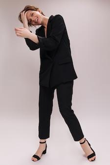 Vrouw die in kostuum op witte achtergrond glimlacht. gelukkige aantrekkelijke dame in zwarte jas en pamts lacht en stelt op geïsoleerd