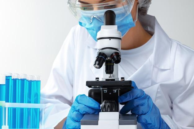 Vrouw die in laboratorium in microscooplens kijkt
