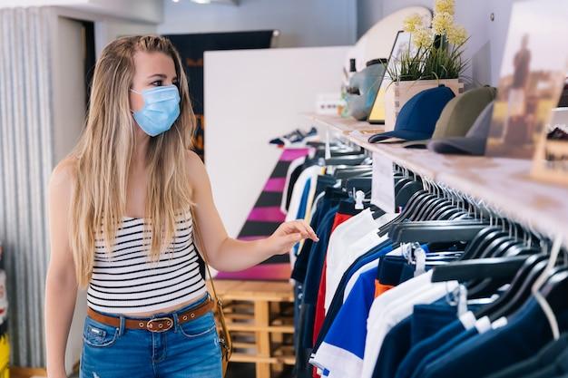 Vrouw die in masker bij een kledingsopslag winkelen in de pandemie van het coronavirus
