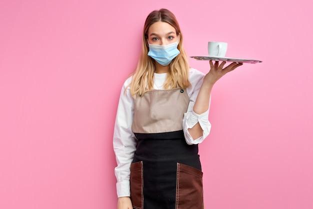 Vrouw die in masker witte klassieke kop voor koffie of thee op dienblad houdt die over roze studioachtergrond wordt geïsoleerd.