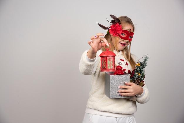 Vrouw die in maskerademasker de giften van kerstmis aanbiedt.