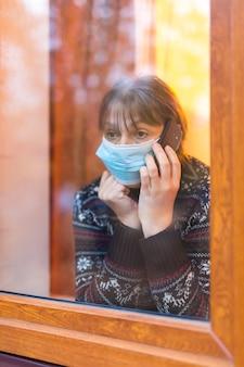Vrouw die in medisch masker door venster met hoop kijkt
