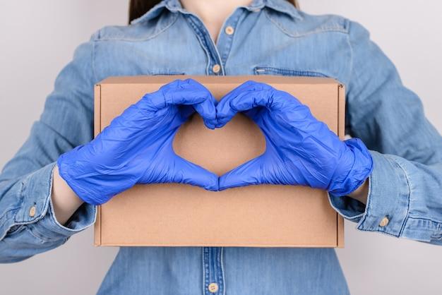Vrouw die in medische handschoenen kartondoos houdt en hart met vingers maakt geïsoleerde grijze achtergrond