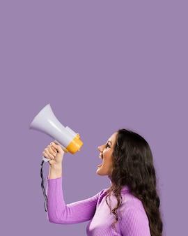 Vrouw die in megafoon en exemplaarruimte schreeuwt