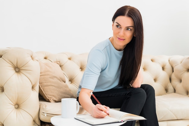 Vrouw die in notitieboekje bij kleine lijst schrijft