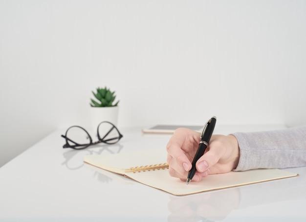 Vrouw die in notitieboekje, het concept van het kantoorwerk schrijft