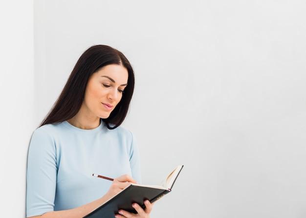 Vrouw die in notitieboekje met potlood schrijft