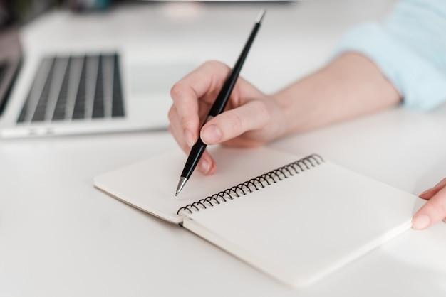 Vrouw die in notitieboekje schrijft