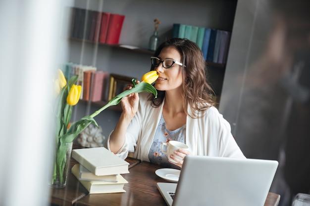 Vrouw die in oogglazen bij lijst met kop thee zitten