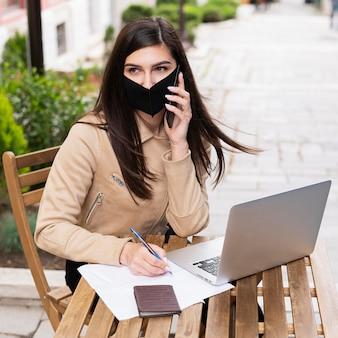 Vrouw die in openlucht aan laptop met gezichtsmasker werkt