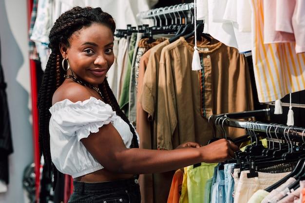 Vrouw die in opslag kleren controleert
