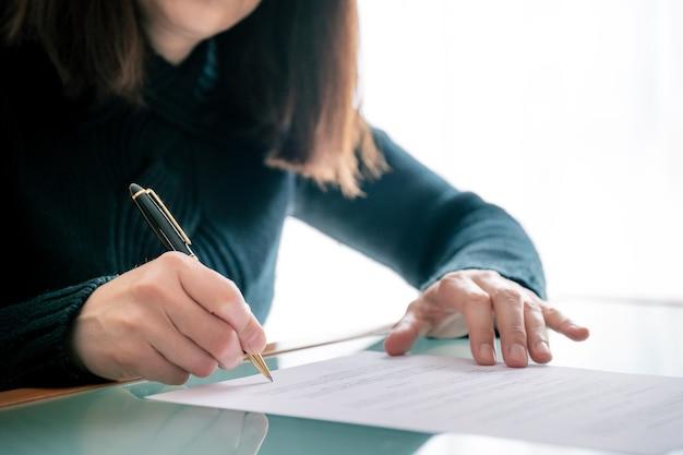 Vrouw die in overhemd document ondertekent