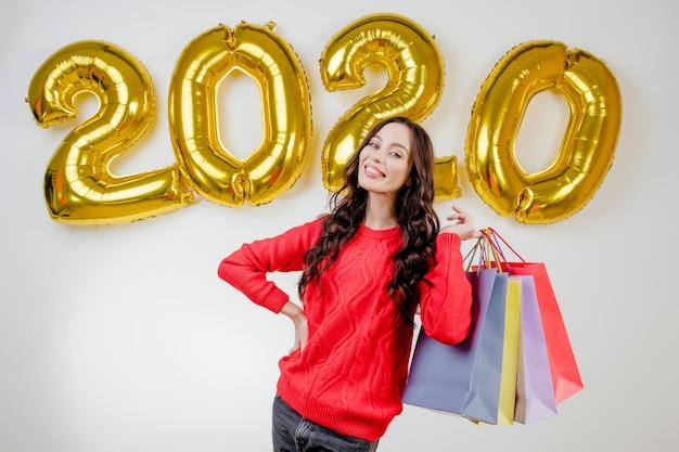 Vrouw die in rode sweater kleurrijke het winkelen zakken voor nieuwe het jaarballons van 2020 houdt