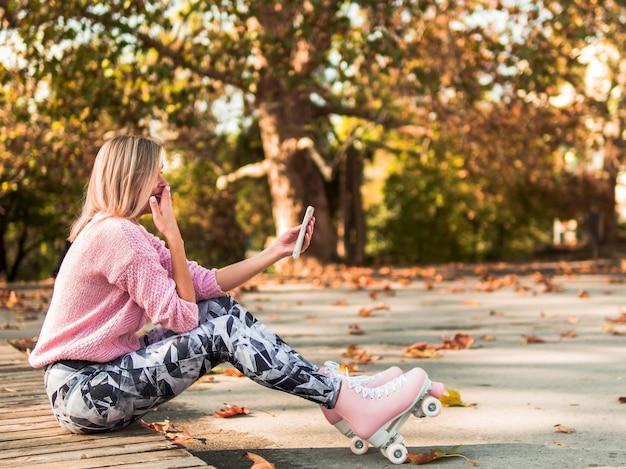 Vrouw die in rolschaatsen om smartphone lachen
