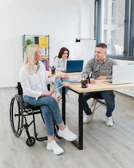 Vrouw die in rolstoel met medewerker bij bureau bespreken