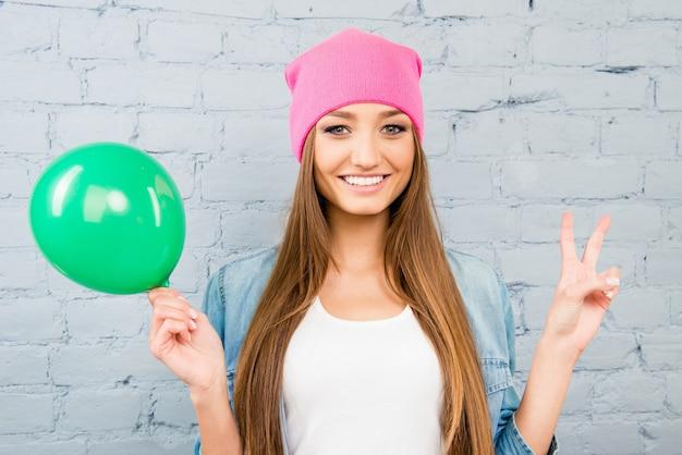Vrouw die in roze hoed groene ballon houdt