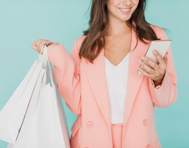Vrouw die in roze jasje bij smartphone glimlacht