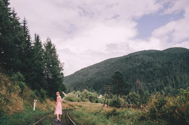 Vrouw die in roze kleding op spoorwegsporen lopen