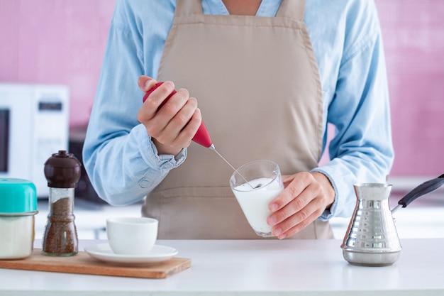 Vrouw die in schort aromatische koffie met thuis het gebruiken van een melkopschuimer maakt