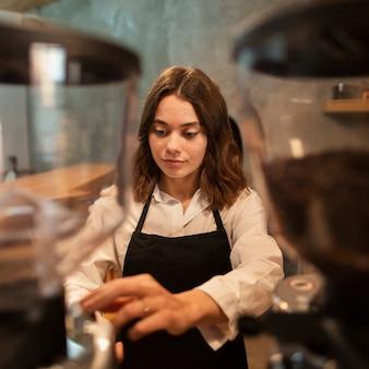 Vrouw die in schort koffie maakt