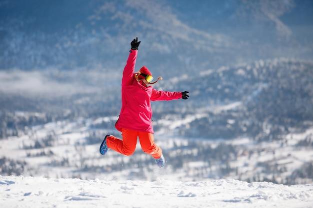 Vrouw die in skimateriaal van blauwe bergketens springt. jas met capuchon, rode broek, skibril. gezonde levensstijl. sport concept. selectieve aandacht.